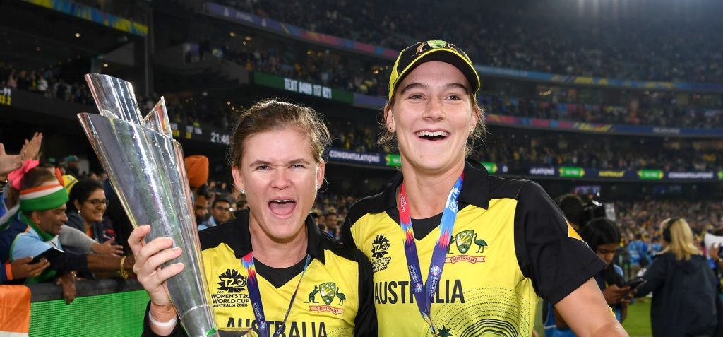 Jess Jonassen (L) and Annabel Sutherland (R) pose with the T20 World Cup trophy. © Getty Images